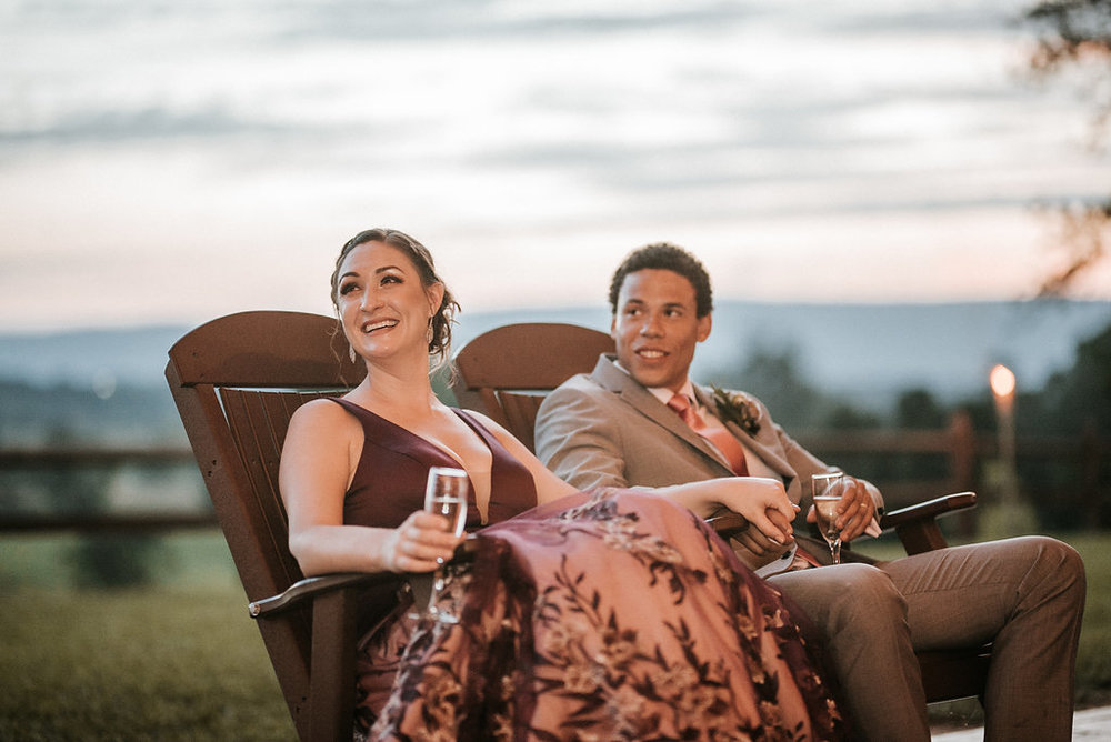 bride and groom sitting in rocking chairs at The Pavilion Shenandoah Woods
