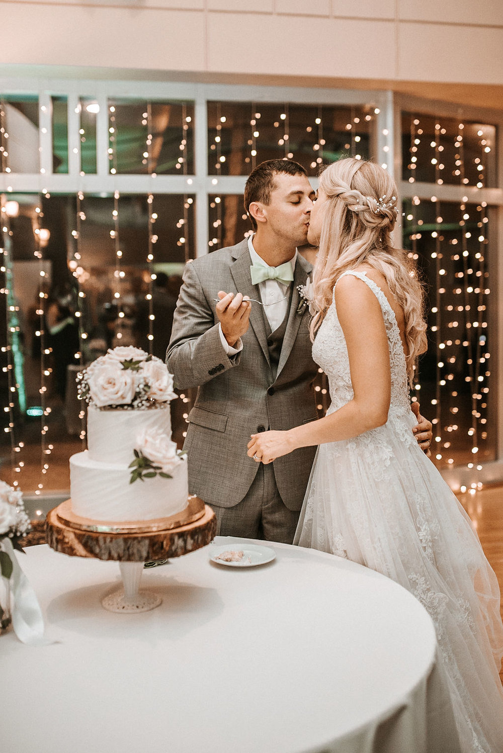 Bride and Groom Kissing While Cutting the Cake at The Woodlands at Algonkian