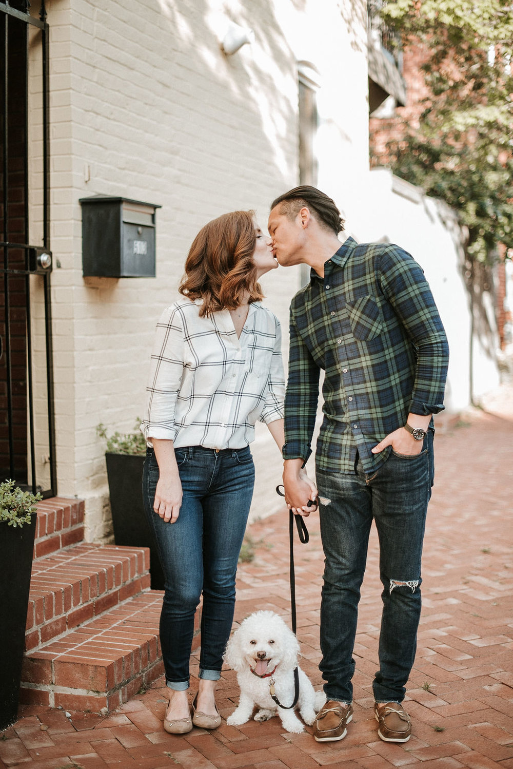 couple kissing featuring their dog during engagement session at H Street in Washington DC