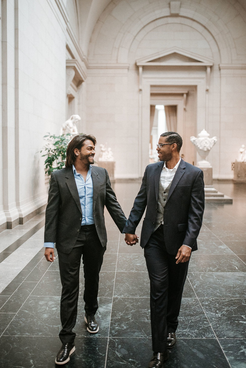 couple smiling and holding hands during an engagement session at the National Portrait Gallery