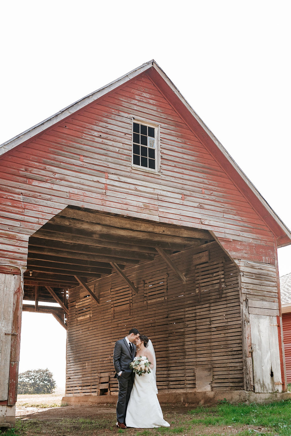 bride and groom embracing in front of a barn at Linganore Winecellars