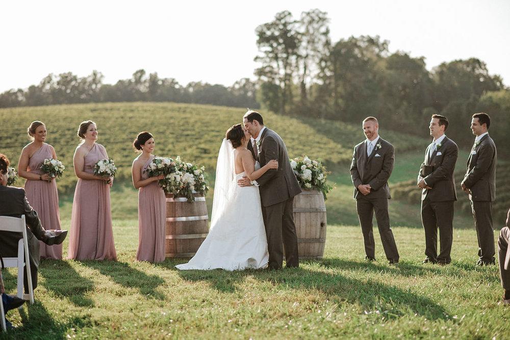 bride and groom kiss at the alter at Linganore Winecellars