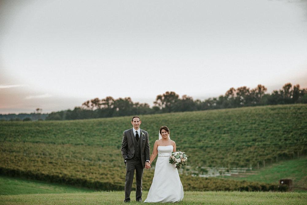 bride and groom holding hands at vineyard at Linganore Winecellars
