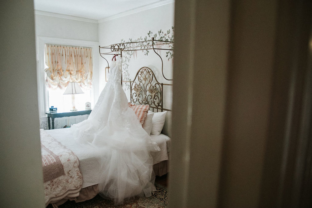 wedding dress hanging from bed at Historic Rosemont Manor