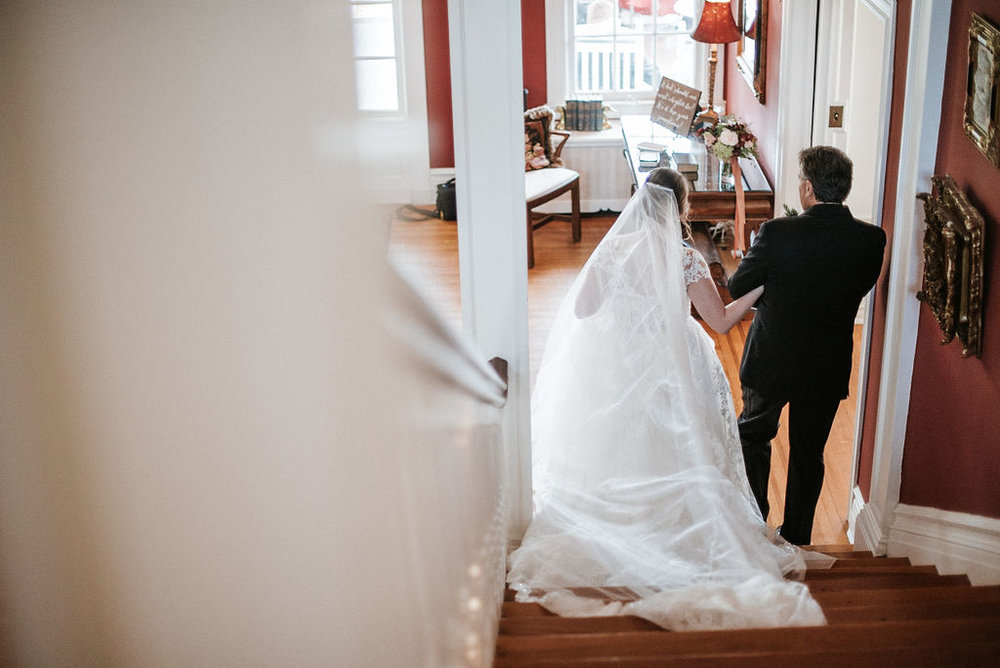 Bride walking down stairs at Historic Rosemont Manor