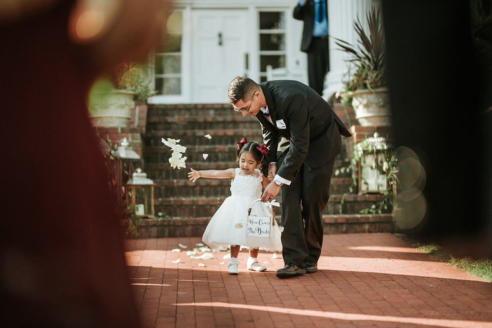 flower girl throwing petals down the aisle at Historic Rosemont Manor