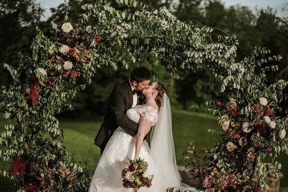 bride and groom kissing under wedding arch at Historic Rosemont Manor