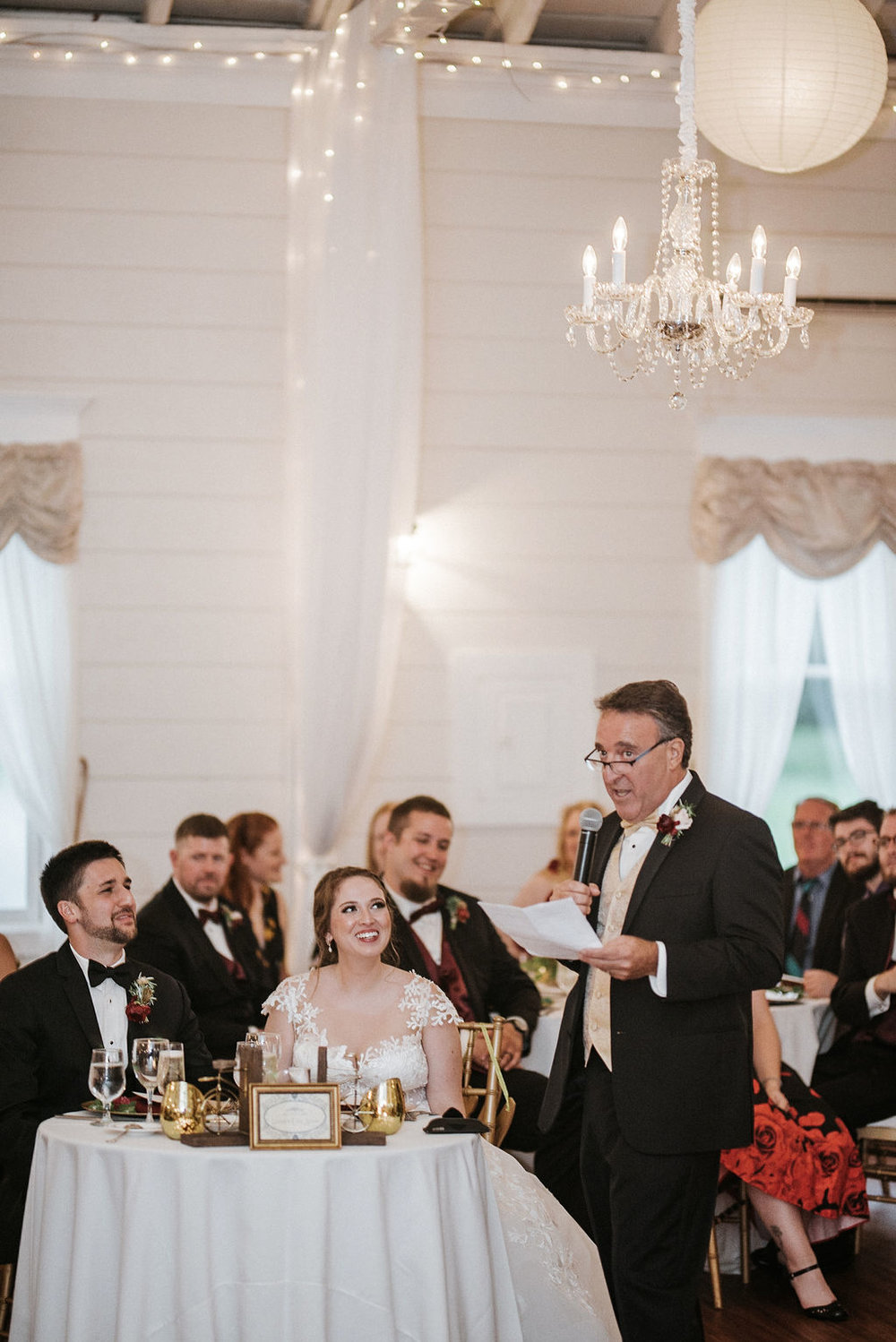 bride and groom listening to father of the bride's speech at Historic Rosemont Manor