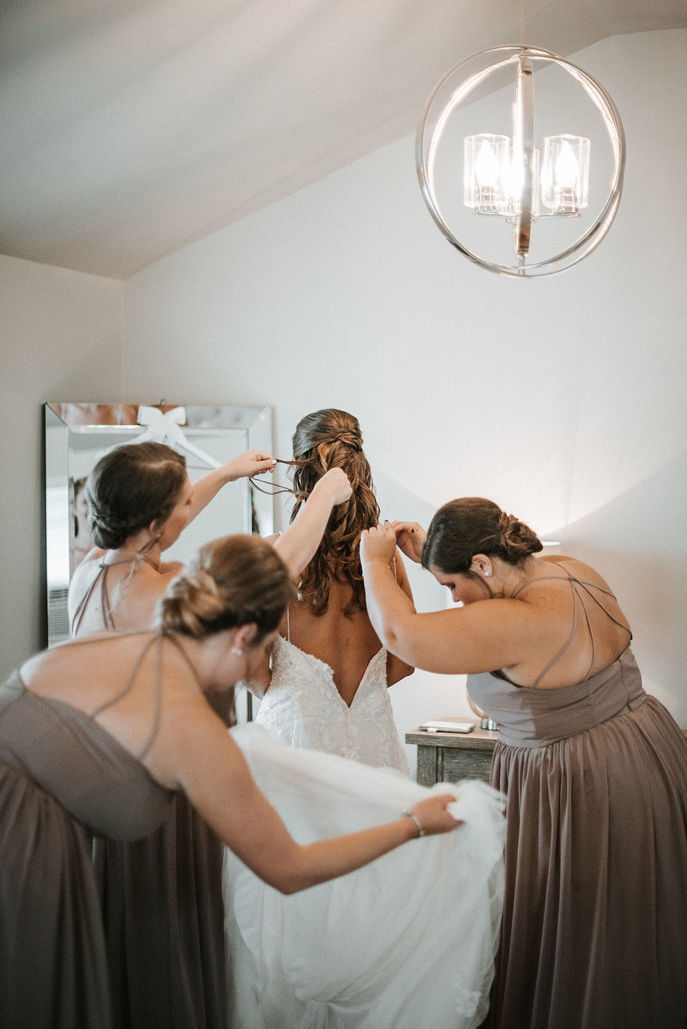 Bridesmaids helping bride get into dress at 48 Fields Farm
