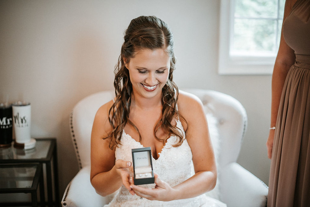 bride putting on earrings at 48 Fields Farm