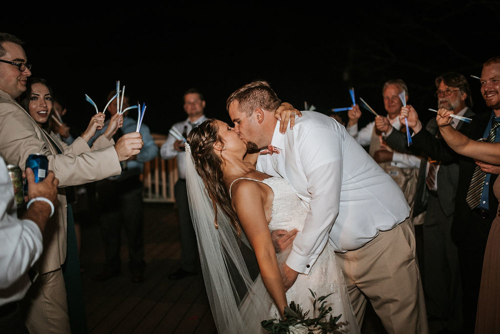 bride and groom kissing as they leave reception at 48 Fields Farm
