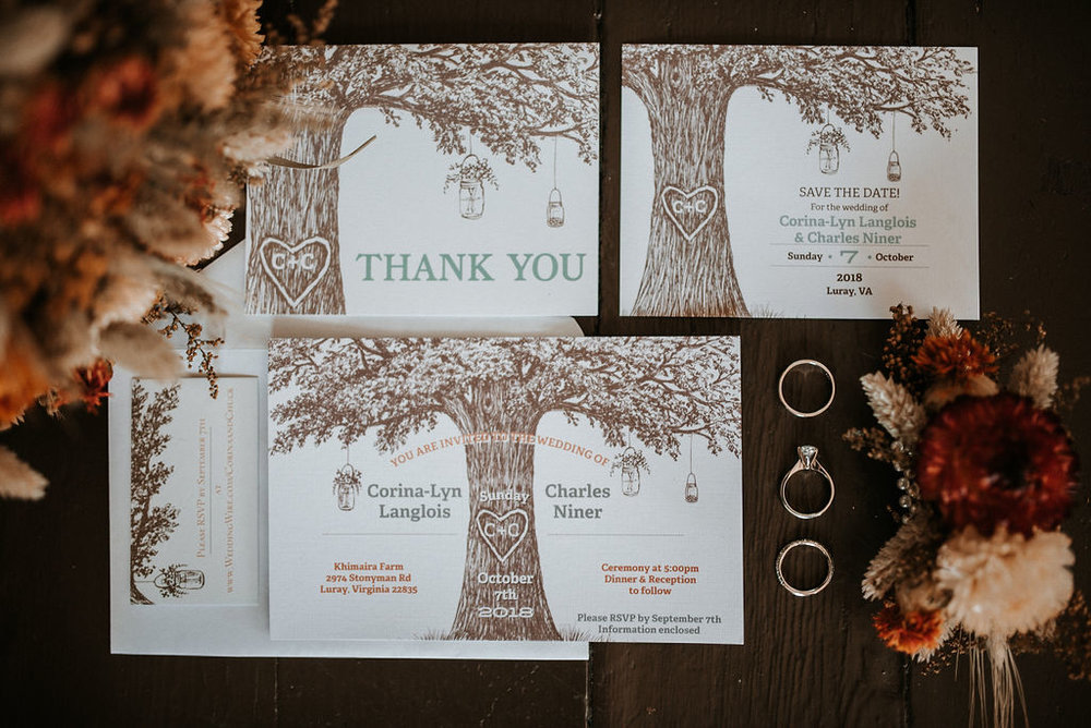 Detail Shot of Save the Dates, Rings, and Flowers at Khimaira Farm