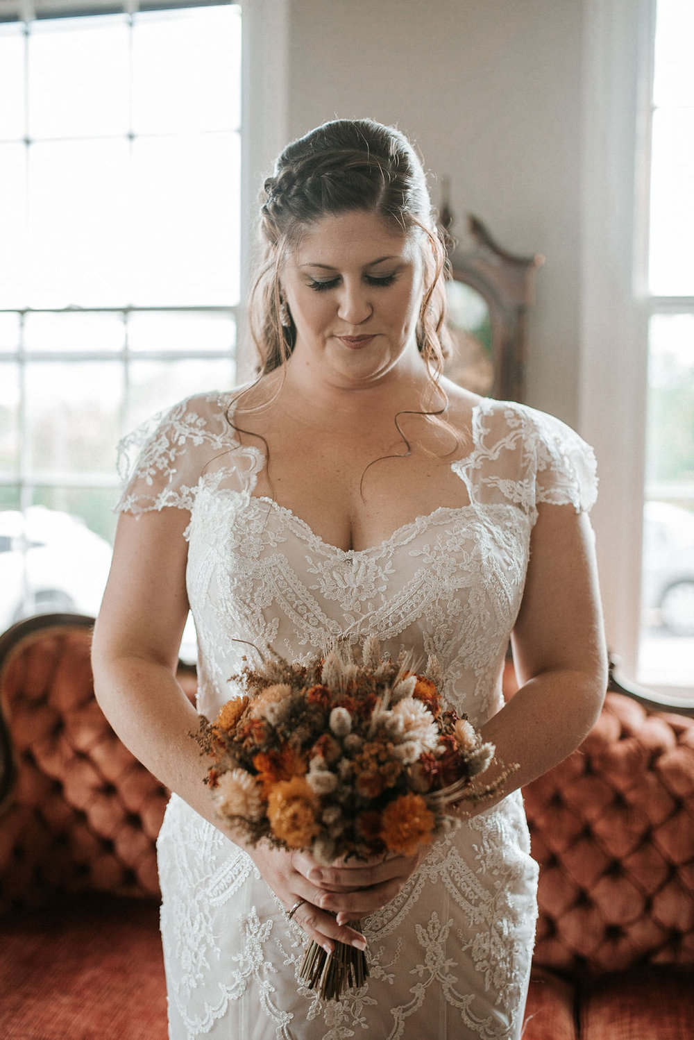 bride holding bouquet and admiring flowers at Khimaira Farm