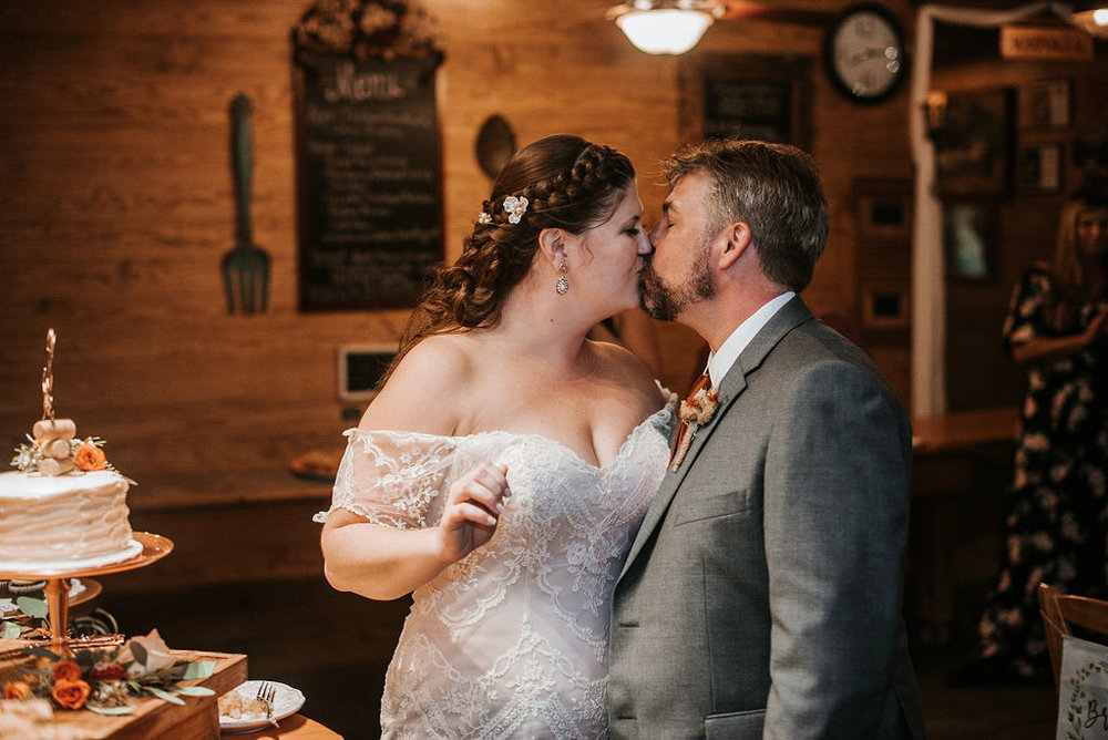 bride and groom kissing after cutting wedding cake at Khimaira Farm