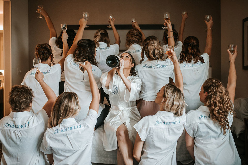 bride and bridesmaids posing and drinking champagne at kimble farm
