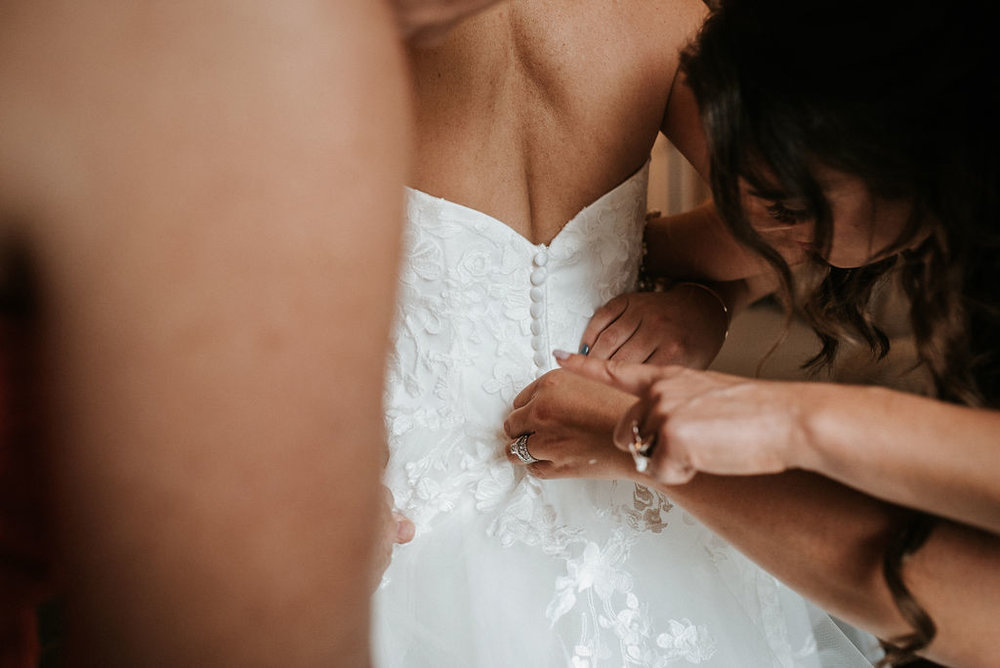 bridesmaids buttoning bride's wedding dress at kimble farm