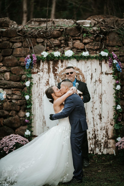 bride and groom kissing at the alter at kimble farm