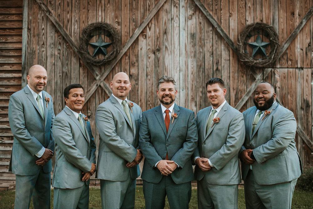 groom and groomsmen smiling and posing at Khimaira Farm