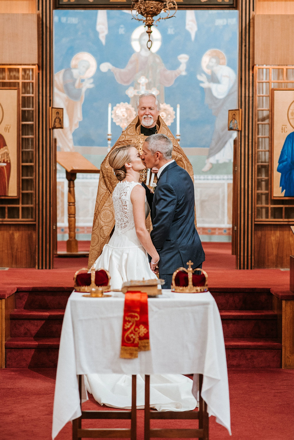 bride and groom kissing at the alter at St. Mark Orthodox Church