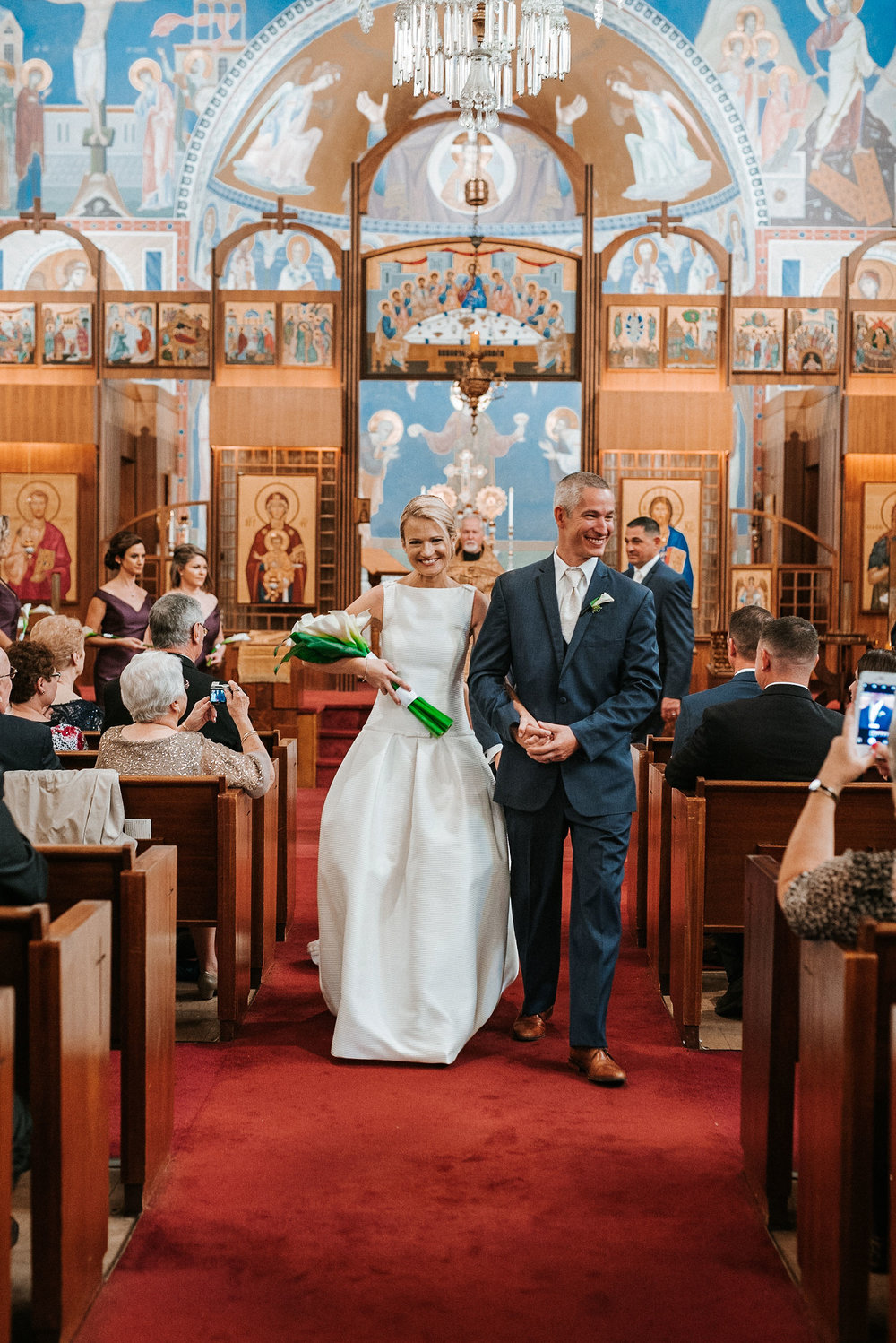 bride and groom walking up the aisle at St. Mark Orthodox Church