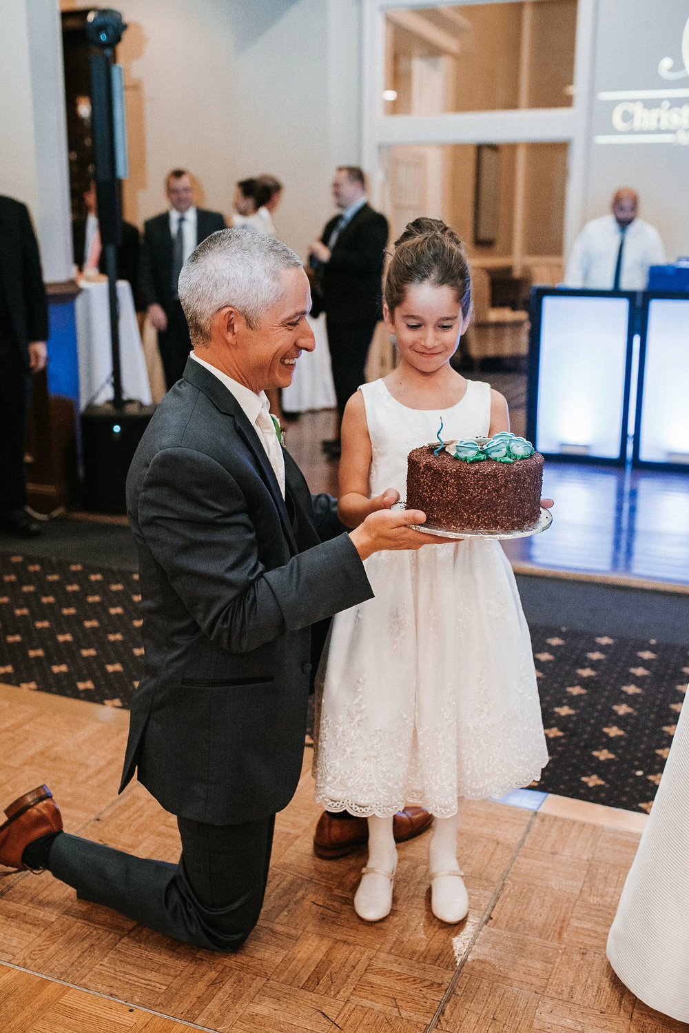 daughter of groom getting birthday cake at wedding at St. Mark Orthodox Church