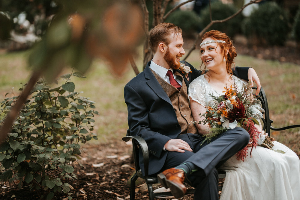 bride and groom sitting on a bench and smiling at Braehead Manor