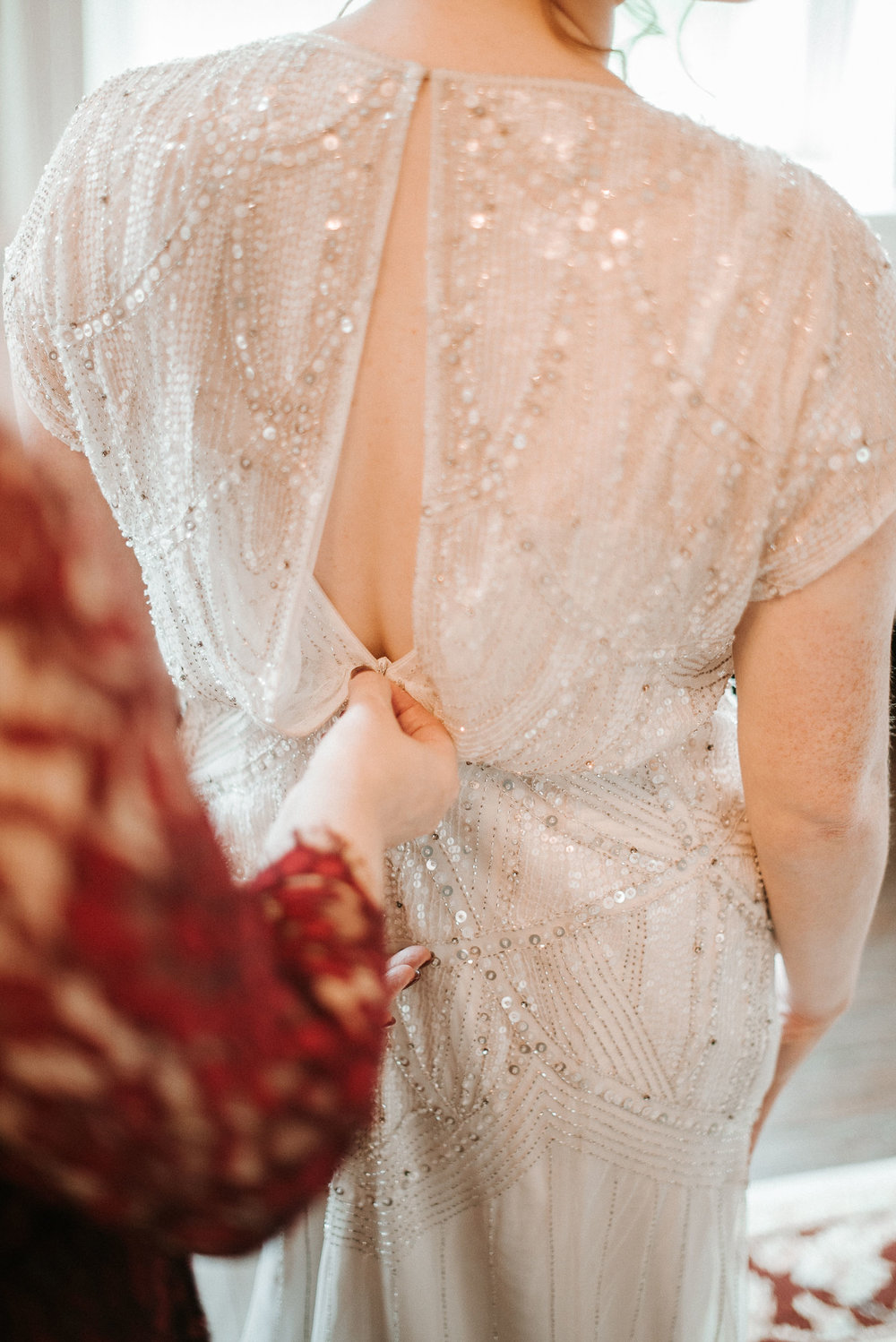 bride getting her dress zipped up at Braehead Manor