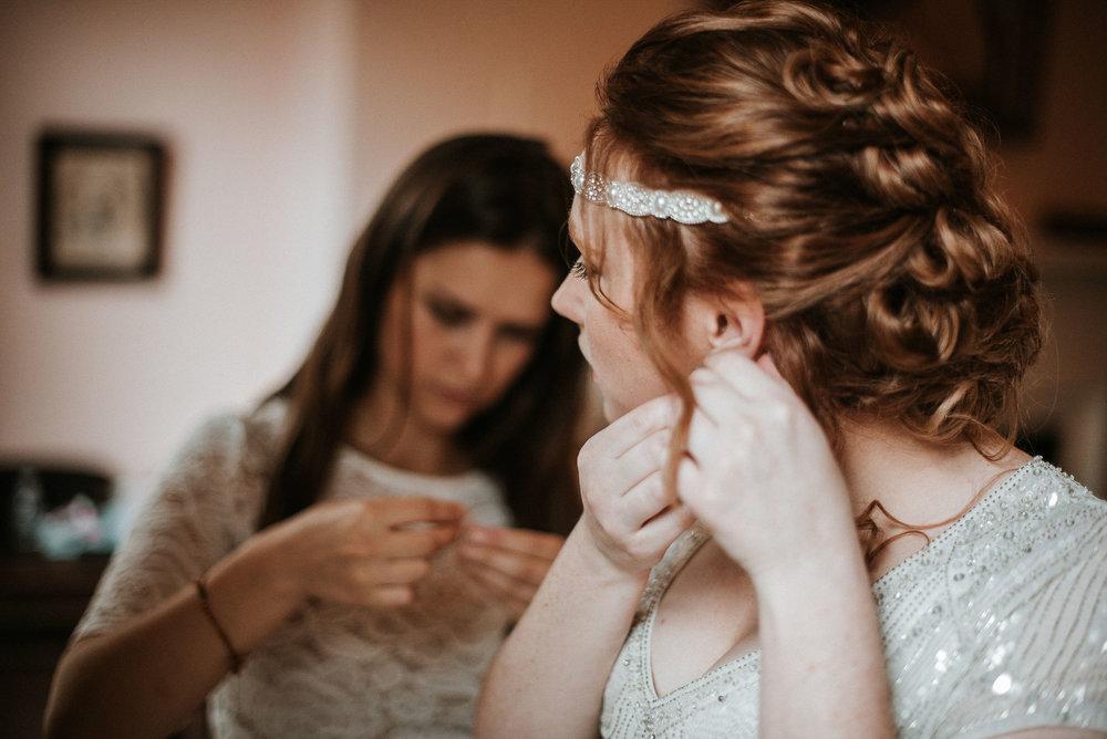 bride putting on earrings at Braehead Manor