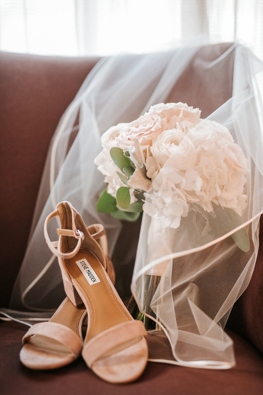 detail shot of bride's shoes, flowers, and veil at Hotel Monaco