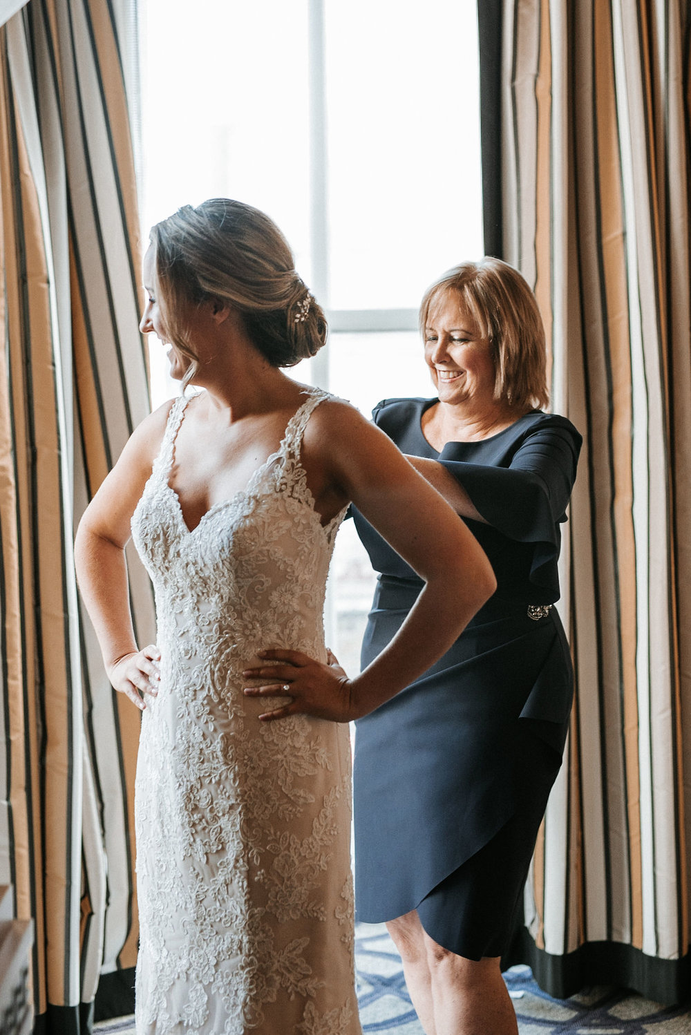 mother of the bride zipping up dress at Hotel Monaco