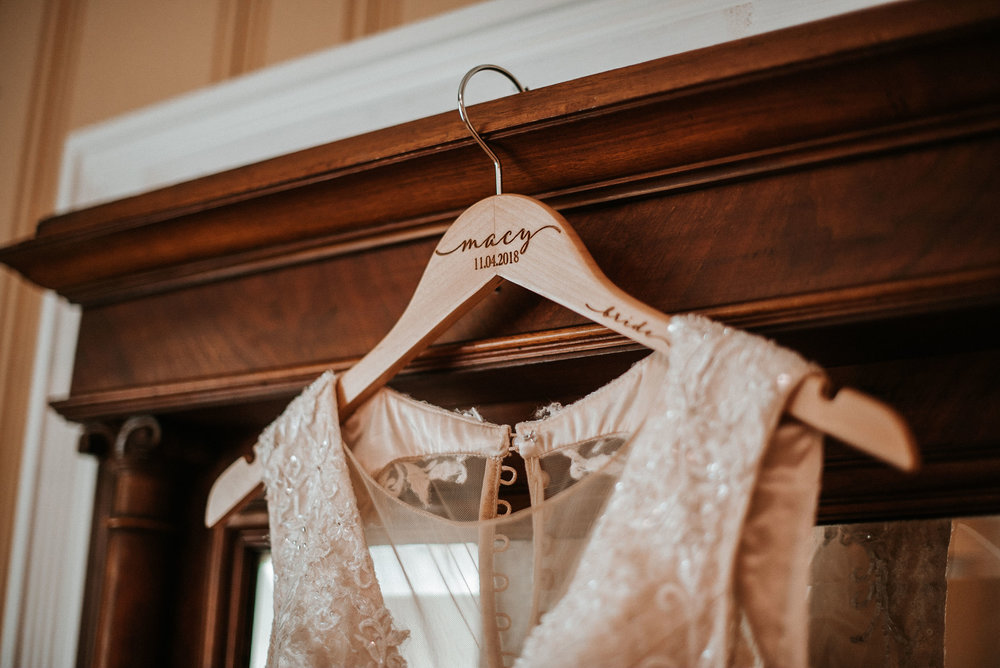 detail shot of bride's wedding dress and hanger at the inn at the silk mill