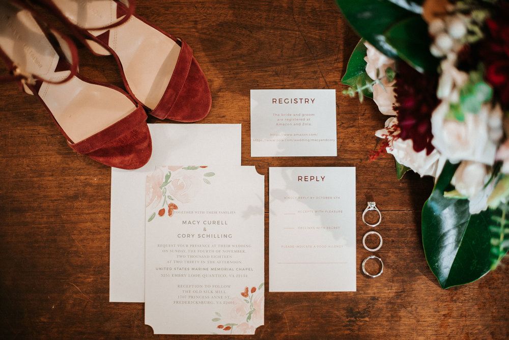 detail shot of bride's shoes, stationery, and rings at the inn at the silk mill
