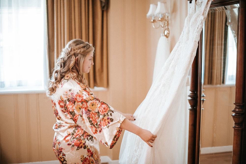 bride admiring her dress at the inn at the silk mill