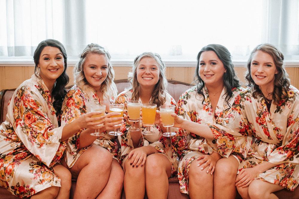 bride and bridesmaids drinking at the inn at the silk mill