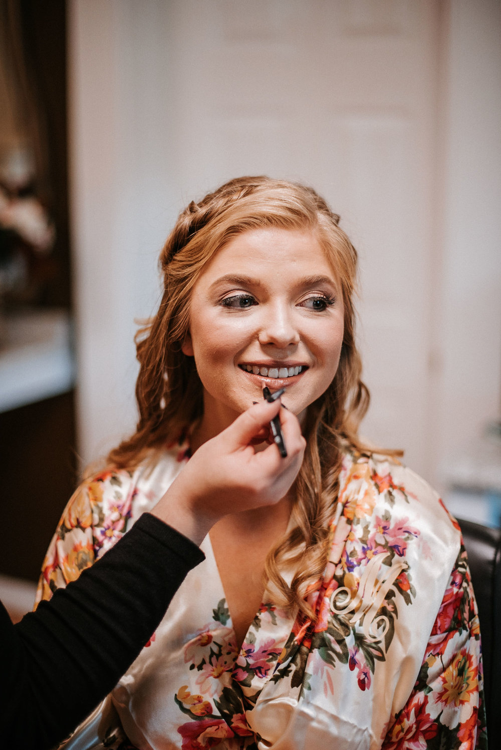 bride getting her makeup done at the inn at the silk mill