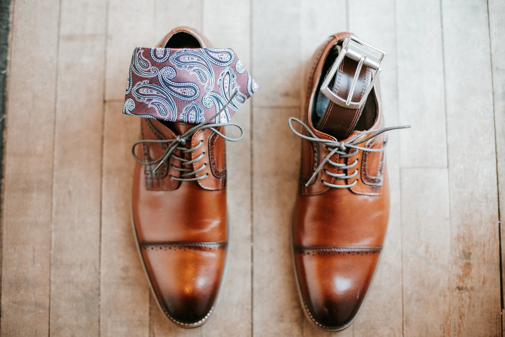 detail shot of groom's shoes, tie and belt at the inn at the silk mill