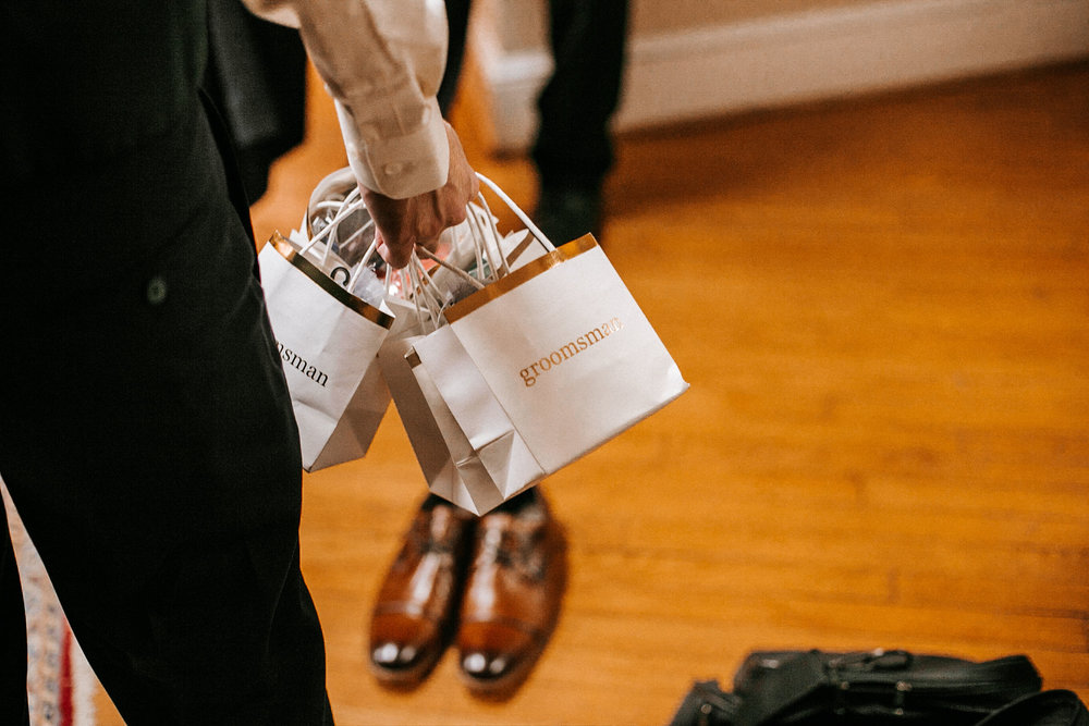 groomsmen holding gifts at the inn at the silk mill