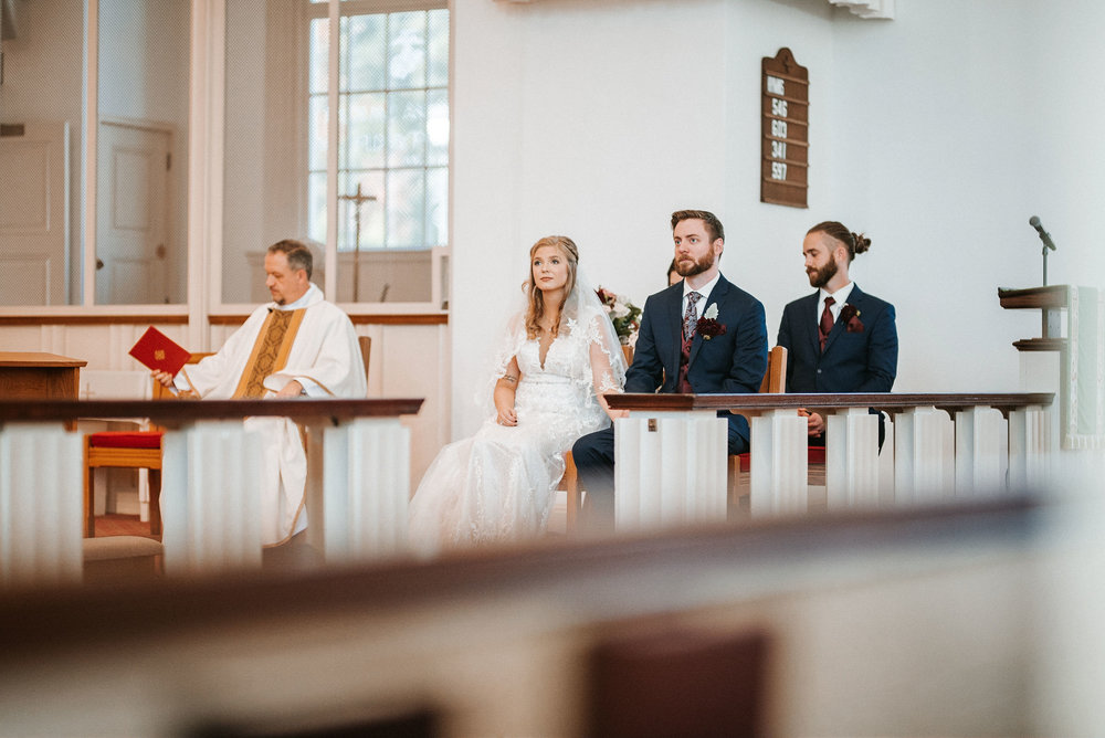 bride and groom sitting down at the united states marine corps memorial chapel