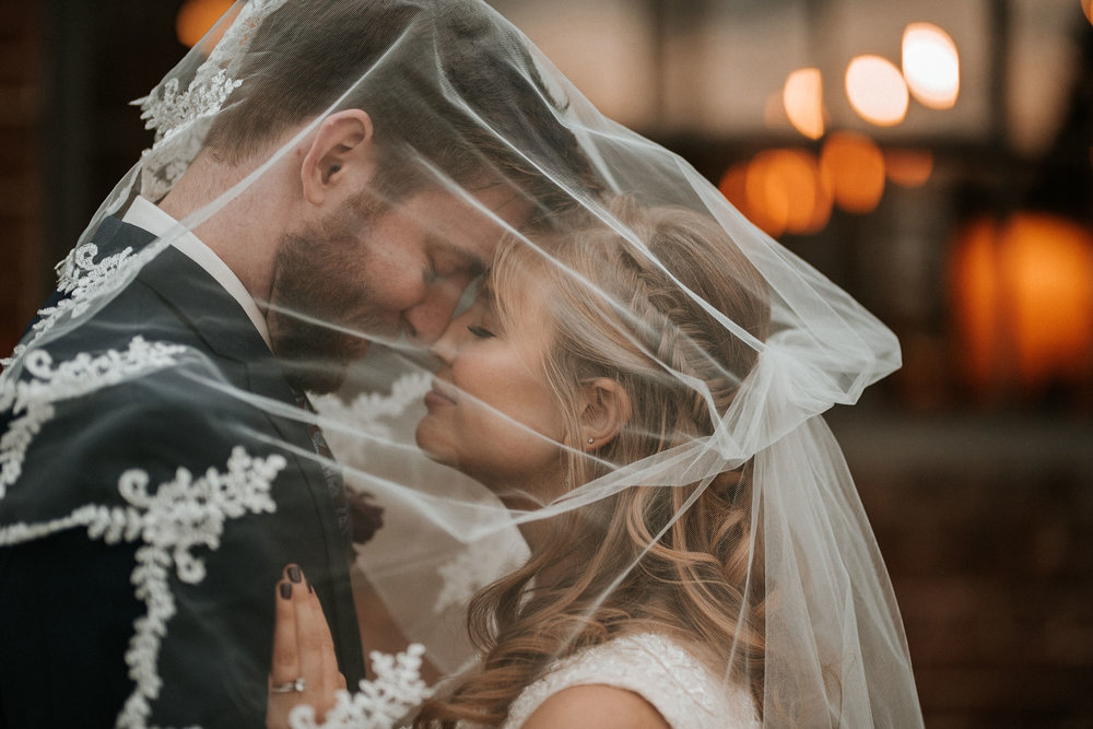 bride and groom under a veil at the inn at the silk mill