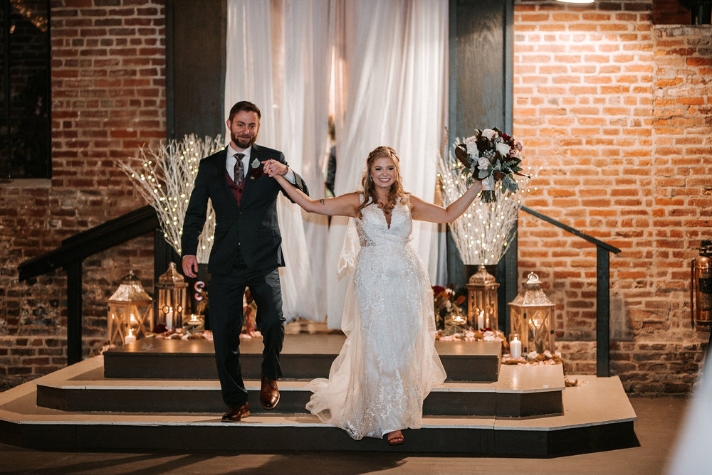 bride and groom entering the reception at the inn at the silk mill