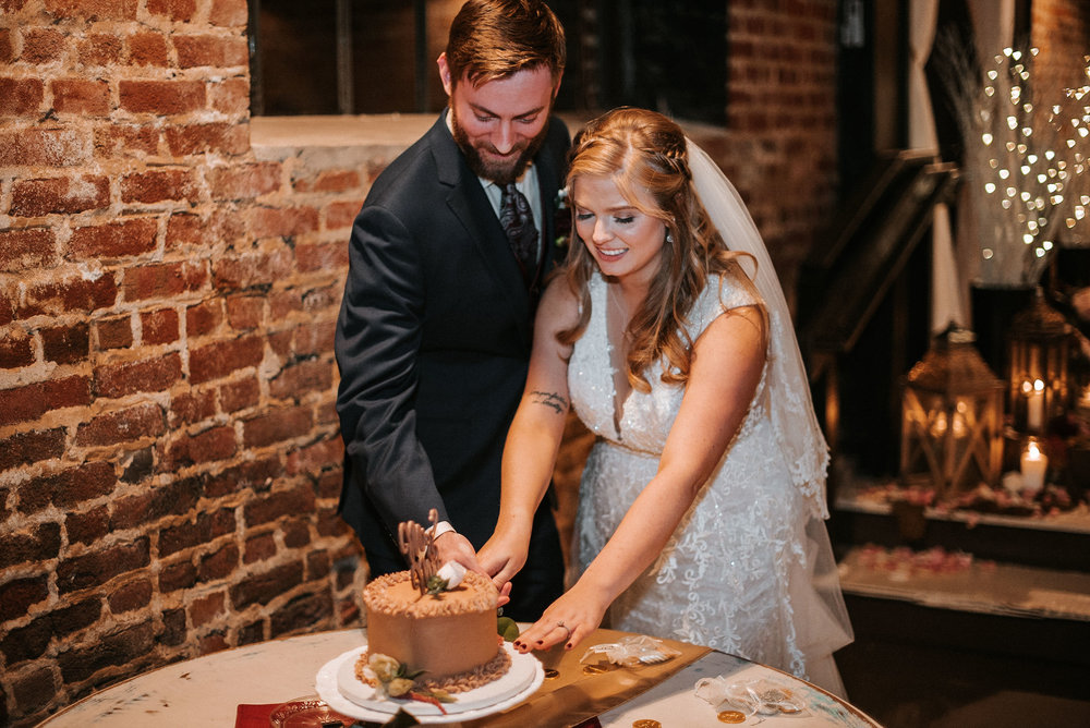 bride and groom cutting the cake at the inn at the silk mill