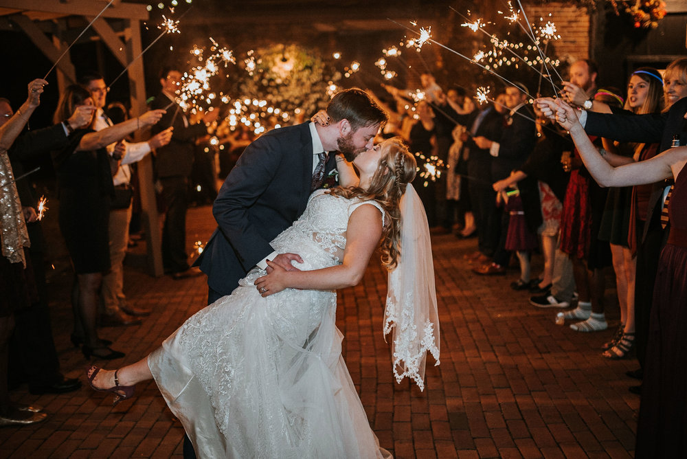 bride and groom kissing under sparklers at the inn at the silk mill
