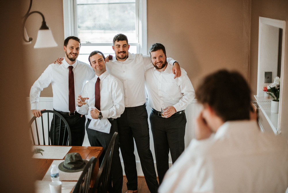 groomsmen smiling at the middleburg barn at fox chase farm