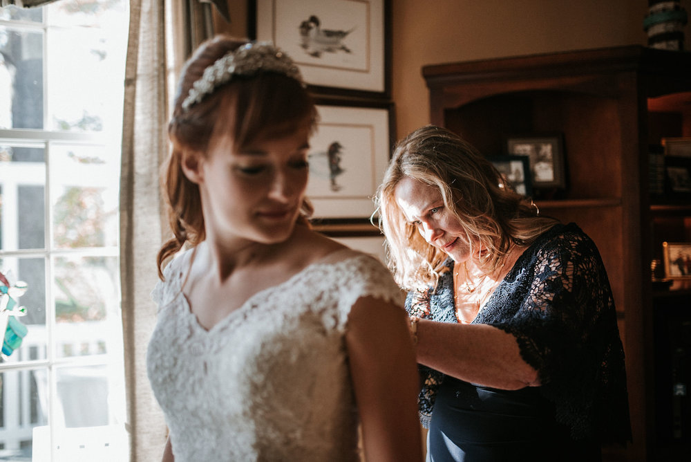 mother of the bride helping bride get in to wedding dress at the middleburg barn at fox chase farm