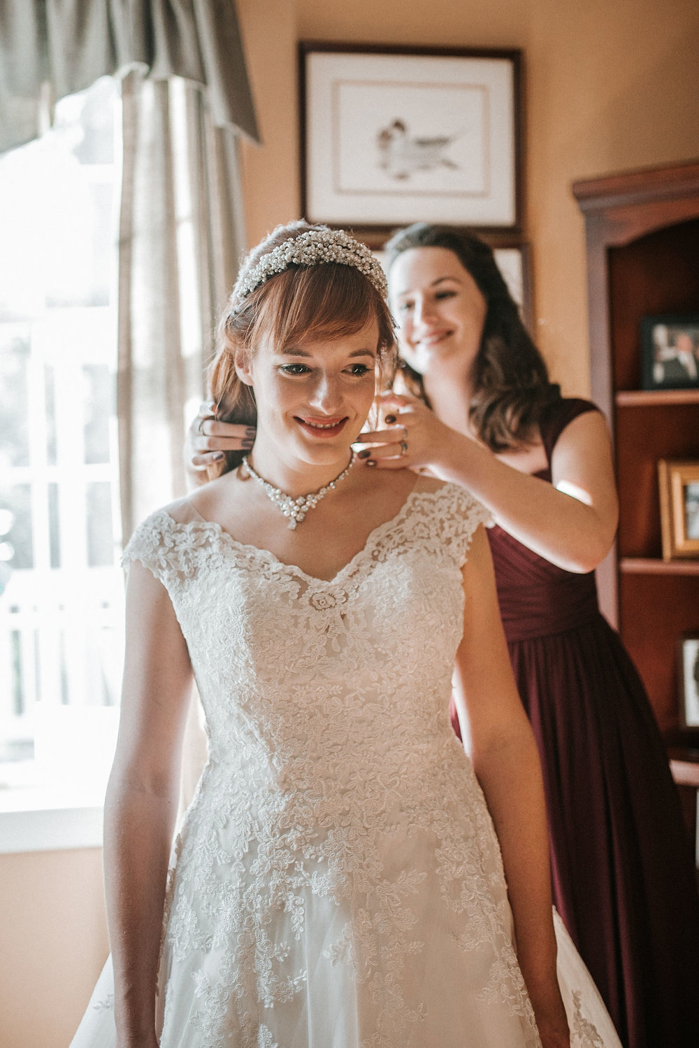 bride putting on necklace at the middleburg barn at fox chase farm