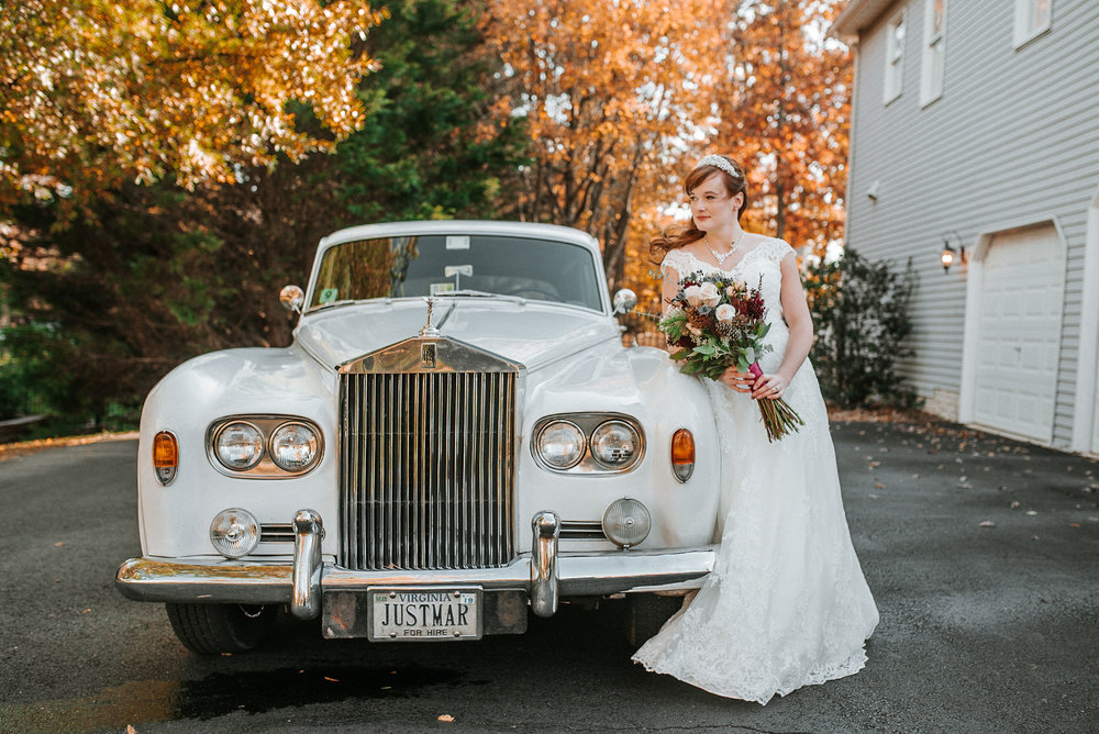 bride leaning on car at the middleburg barn at fox chase farm