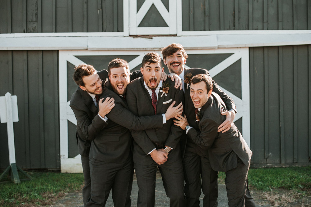 groom and groomsmen laughing at the middleburg barn at fox chase farm