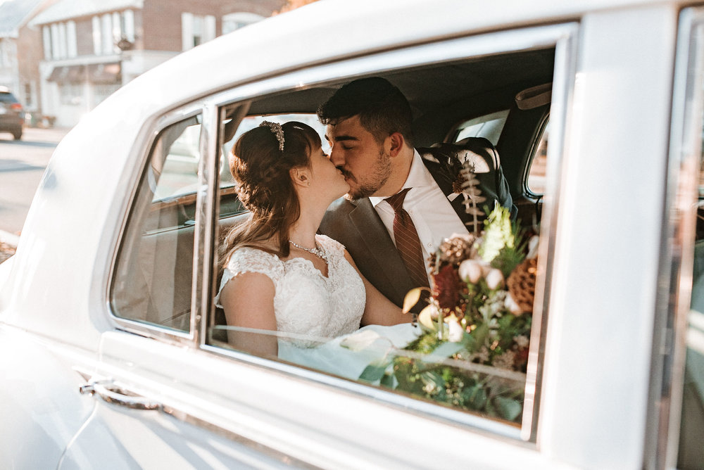 bride and groom kissing inside car at the Middleburg United Methodist Church