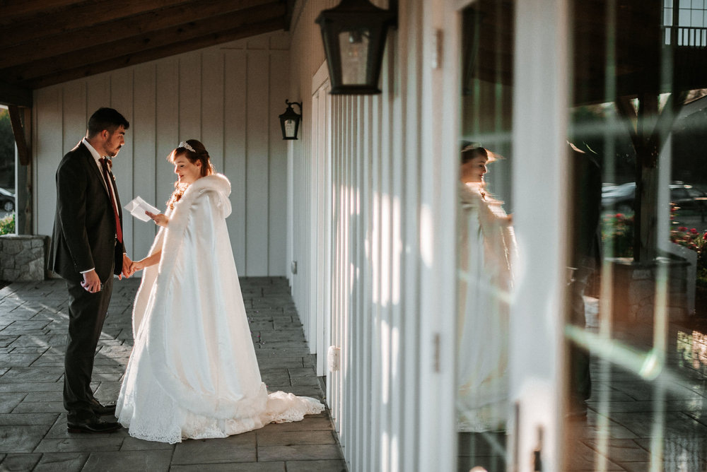 bride and groom reading letters at The Middleburg Barn at Fox Chase Farm