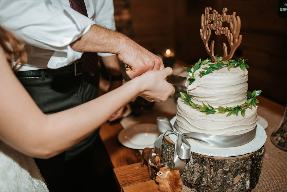 bride and groom cutting cake at The Middleburg Barn at Fox Chase Farm